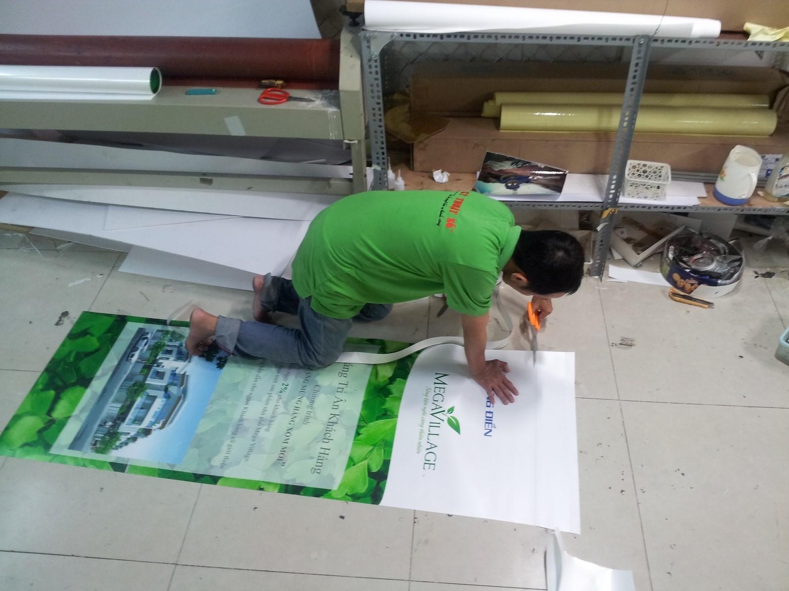 Nhân viên CongTyInNhanh đang gia công thành phẩm poster banner PP cho khách hàng